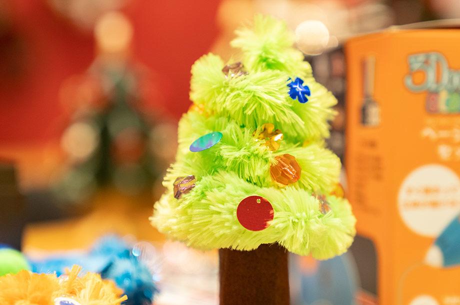 モールやボーズなどのパーツを使ってクリスマスツリーを作っている画像